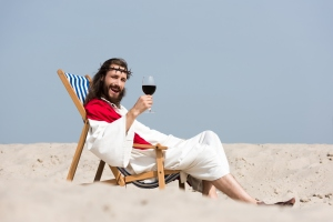 smiling Jesus in robe and red sash resting on sun lounger with glass of red wine in desert, looking at camera